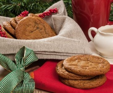 Einkorn Christmas Cookies in a bowl covered with brown burlap cloth and a red cup filled with coffee