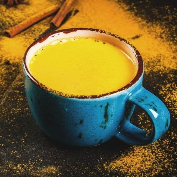 golden turmeric milk in a blue cup to relieve joint pain naturally