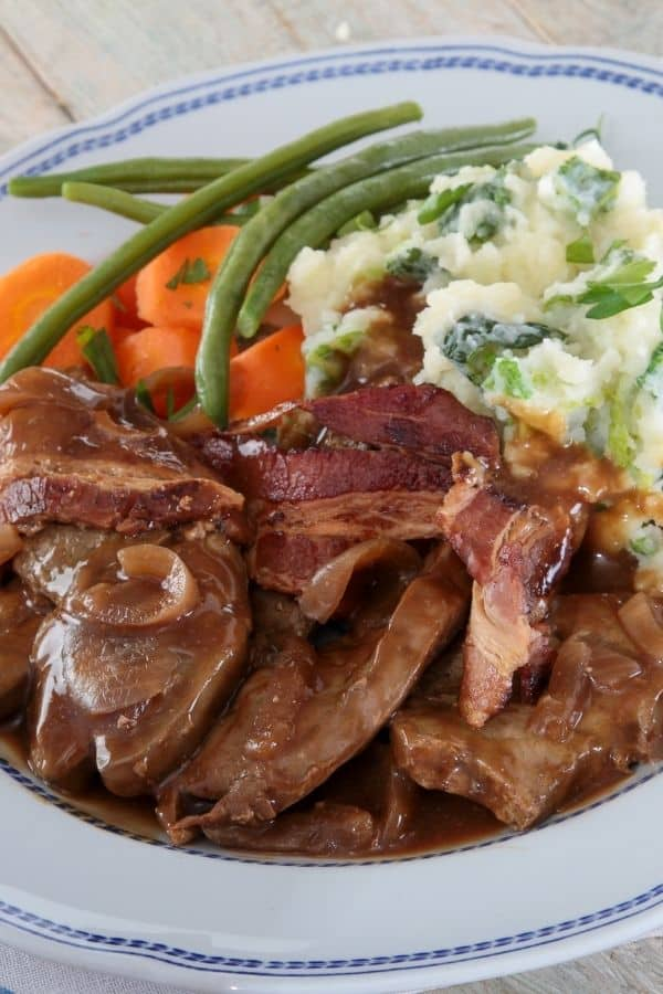 liver an onions recipe on a white and blue plate with carrots and mashed potatoes