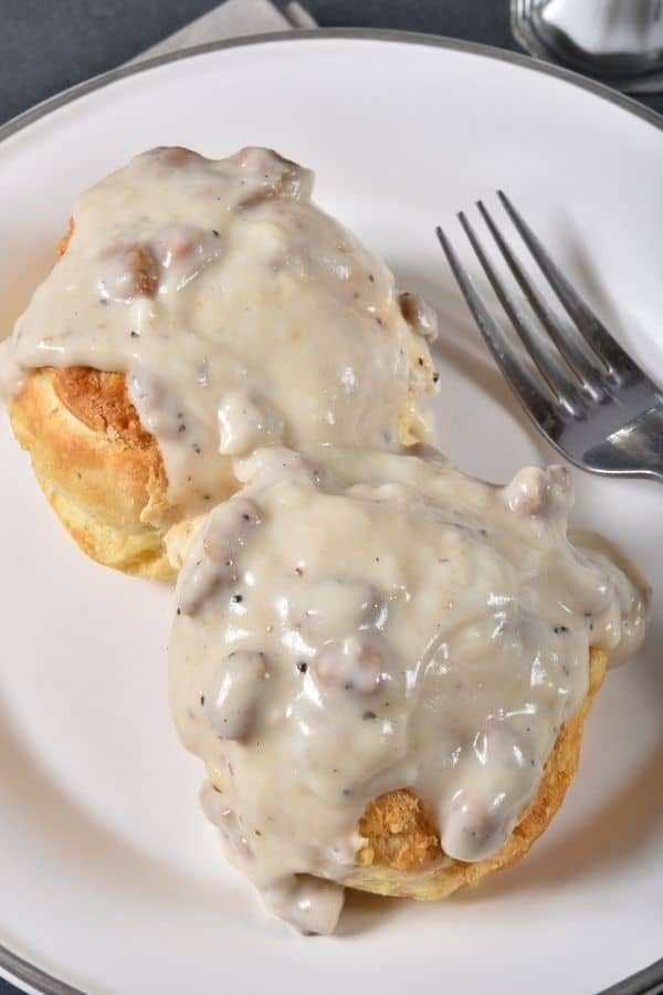 Sausage gravy on biscuits on white plate