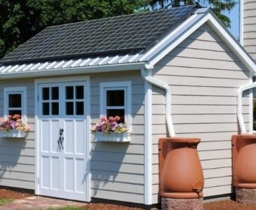 beige shed with solar panels and rain water collection barrels for converting a shed into a tiny house